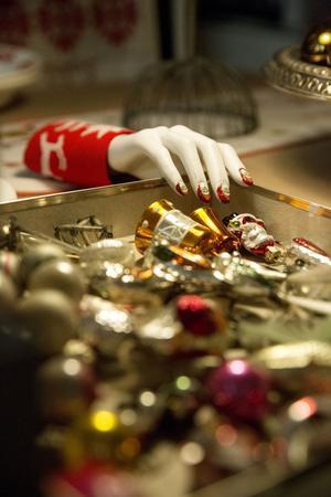 Skyltdockor är Karin Ferner svag för. Den här skyltdockshanden, som verkar vilja fingra på Karins julkulesamling,  har fått jultomtemanikyr och ett armband sydd av en gammal julduk.