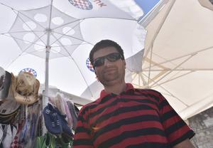 Nicola från Zagreb säljer handdukar, hattar och solglasögon i Hvar. Han tycker att han har det perfekta sommarjobbet.
