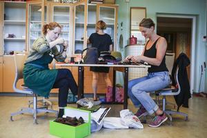 Systrarna Ebba och Sofia Okfors tillverkar kepsar.