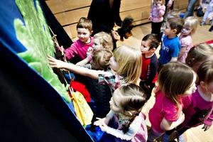 Efter att Minne Hägglund berättat om apan Fin fick de nyfikna barnen känna på apan, trädet, hunden och vattnet. Foto: Annakarin Björnström