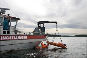Brandmännen arbetar metodiskt och samspelt. Niklas Bruhn hoppar i för att ta de nödställda till båtens bår så att hans kollegor kan hissa upp dem.