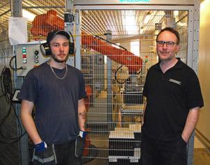 Robin Andersson och Björn Falkeström övervakar roboten som ställer öllådorna på lastpallar.