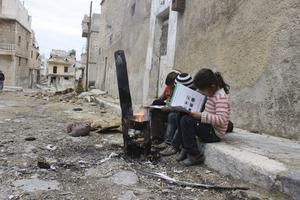 Skolor, sjukhus, lekplatser – alla pekas ut som farliga områden för barn att vistas på i rapporten från FN.  Här studerar några barn ett informationsblad från FN om riskerna med att närma sig okända föremål.