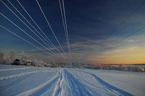 Alexander Estmo har tagit en bild där elledningarna kompletterar bilden på ett mycket bra sätt tillsammans med skid- och skoterspåren i snön. Oftast brukar elledningar kunna vara i vägen vid landskapsfotografering, men på den här bilden har fotografen istället använt sig av dem för att uppnå en estetisk effekt. Bilden är bra exponerad med klara färger, som den gula färgen i horisonten och den cyanfärgade snön tillsammans med den blåa himlen.