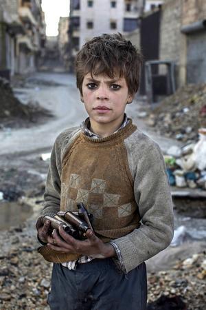 Nioårige Alladin samlar tomhylsor vid syriska frontlinjen och säljer. Arbetet är farligt. Årets bild 2014.