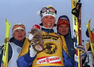 Magdalena Forsberg. Översta på prispallen, med den gula ledarvästen på sig och med ett härligt smittande guldleende. Så minns vi Medelpadsidrottens främsta genom alla tider.