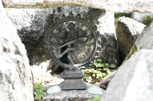 Här och där bland stenar och växter finns små statyetter och symboler, de flesta är från Indien.