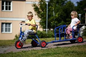 Cykeltåg. Daniel Söderberg och Martina Bergstedt tar en tur runt gården utanför förskolan Vinden. Foto:Janne Eriksson