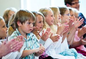 Förväntansfulla barn applåderar åt elevernas framträdanden.