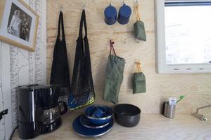 Längs ena långsidan i huset löper en bänk med hyllor och på väggen hänger det muggar och påsar i karbinhakar. Här finns det mesta som behövs på liten yta.