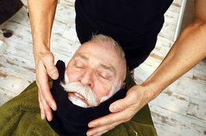 Det är viktigt att värma innan man börjar raka förklarar barberaren Emanuel Özel medan han lägger på en varm handuk på kunden Hans Karlsson.