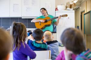 En  förskolepedagog spelar gitarr med barnen på en förskola.