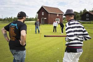 Projektledare Rasmus Ullström och ledaren Tomas Eriksson kollar när deltagarna puttar på greenen.