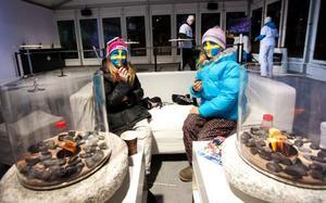 10-åriga Emma Mähl och Ottilia Wallin från Östersund tyckte att det var för kallt ute, men de visade med sina målade ansikten att de hejade på Sverige samtidigt som de satt inne vid elden och mumsade på choklad.Foto: Håkan Luthman