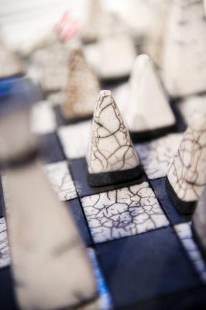 Kontrasten mellan ruffa oglaserade och metalliskt blanka ytor ger spännande effekter. Det har Maria Luksepp utnyttjat i schackspelets rutmönster.