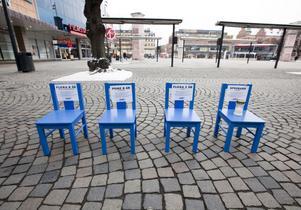 SYMBOL. Fyra blåa stolar, på en av dem brinner ett gravljus. Stolarna är en symbol för att tre av fyra barn som insjuknar i cancer i Sverige överlever.