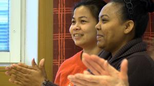 Två av SFI-eleverna applåderar när deras klasskamrat framför en sång på arabiska.