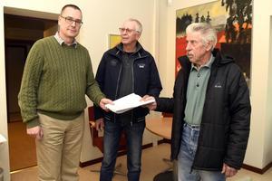Kommunalrådet Mikael Thalin (C) tar emot ett remissvar från,  Sörmedsjöns byförenings Rolf Almstedt och Börje Andersson inne i kommunhuset i Orsa.