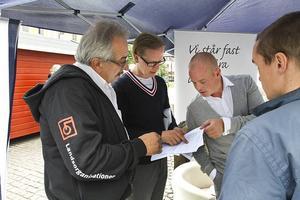 LO-distriktets Seko-representant Ronny Beyer försöker med Sverigedemokraterna reda ut situationen där två politiker samtidigt och intill varandra fått tillgång till varsin mikrofon.