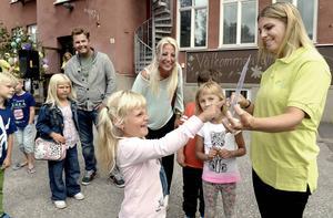 Melisa Carström pekar på sitt namn på den skylt som läraren Mari Burman håller i. I bakgrunden mamma Annika Carström.