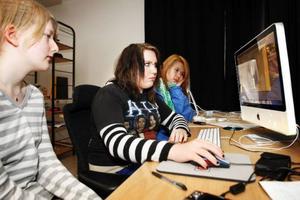 Ottilia Hagelqvist (till vänster) och Lizette Falkstigen (till höger) kollar när Elina Eriksson bearbetar självporträtt till hennes bildspel – ett av jobben i IDA-projektet som nu rullat sitt första år hos Filmpool.