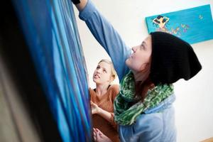 Linnea Jägemar och Emma Sandqvist får målningen på plats.