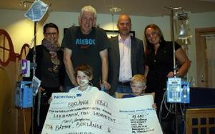 Lekterapin fick ett väldigt fint tillskott på 42 000 kronor efter helgens Må Bättre-lopp. Här håller elvaårige Johan Thollander och nioårige William Nordenvärn upp checken.Bakom står lekterapeuterna Linda Belin och Mats Hildén, medarrangören Dala-Demokr