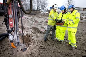Anders Teljebäck (i mitten) och Hans Stergel (till höger) får instruktioner av en av NCC:s medarbetare om hur man sköter borren. Därefter kunde duon inviga byggstarten av nya Lögarängsbadet.