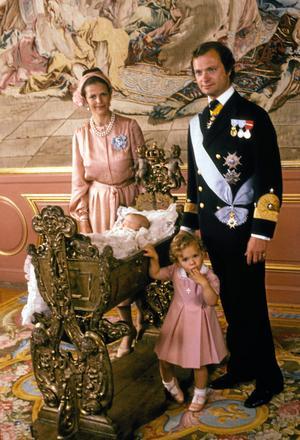 Kronprins Carl Philip ligger i Karl XI:s vagga omgiven av den svenska kungafamiljen, drottning Silvia, kung Carl XVI Gustaf och prinsessan Victoria efter dopceremonin för Carl Philip på Stockholms slott 31:a augusti 1979.