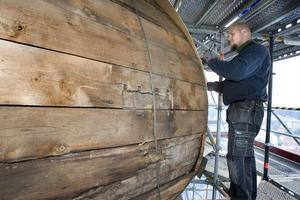 Jimmy Bodin hamrar fast perforerad masonit på träet, innan den nya kopparplåten ska läggas på.