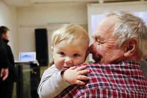 Kvällens yngsta deltagare, Nils-Olof, satt tryggt i farfar John-Erik Bloms famn.