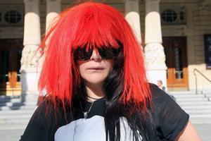 Emma Broomé i solglasögon och röd peruk à la Franka Potente.