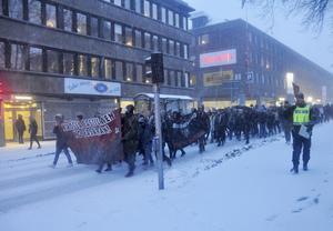 Längs gatorna drar tåget från Stortorget till Södermalmstorg. Polisen stoppar trafiken. Ramsor mot fascism hörs och bengaler tänds.