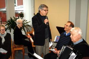 Bagarbesök. Roland Wolmesjö med mikrofonen i handen presenterar Karl-Åke Bothvidsson. Vid pianot Inga-Maria Karlsson och bakom dragspelet sitter Roland Karlsson.