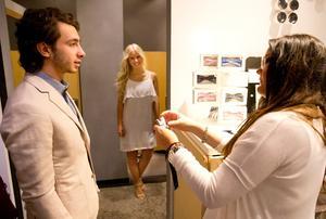 """Ljus kavaj. Salari i linnekavaj för 1699 kr och blåmönstrad skjorta för 599 kr, från MQ. Säljaren Madeleine Johansson hjälper honom välja fluga. """"Nu blev det jobbigt """"säger Salari, som gärna skulle vilja byta ut sin mörka kostym som han redan köpt, mot en ljus outfit till utspringet."""