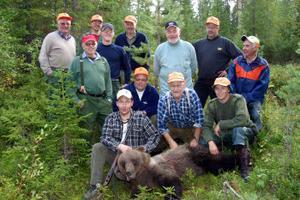 Stefan Höglund med sin första fällda björn och hela jaktlaget som han lovade att han ska bjuda på en bit björnkött.