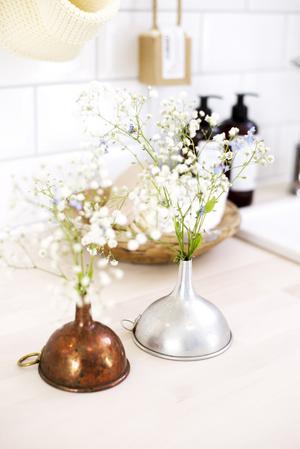 Enligt Elsa Billgren kan i princip alla loppisfynd bli en vas eller en kruka. Här har hon ställt små blommor i Kockumtrattar. Under trattarna döljer sig små snapsglas med vatten i.
