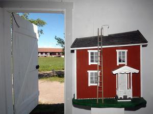 Leif Nordlöf visar ett par av sina trähusmodeller på utställningen. Förlagan till det här huset hittade han i Viksjöfors.