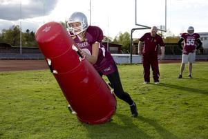 """hårt. Blåmärken och rivsår får man räkna med när man spelar amerikansk fotboll. Även om man bara tacklar en stor, röd säck. Här attackerar VLT:s reporter Emelie Nilsson sin """"motståndare"""". Foto: Per G Norén"""