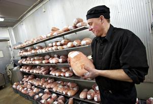 Fjärde advent kommer de här skinkorna att vara hämtade. Mikael Dilén håller en skinka som håller länge tack vare att den är kokt länge på låg värme i vakuumförpackningen.