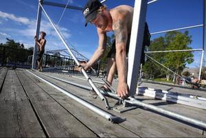 Rickard Kanebo och John Westlund sätter upp ett tält vid hamnen.