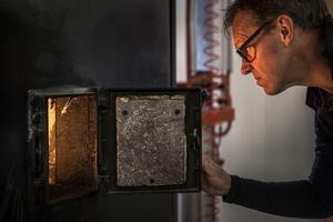 Per Linqvist kontrollerar att kroppen ligger rätt under hela förbränningen. Då och då flyttar han på kroppen för att förbränningen skall vara optimal.