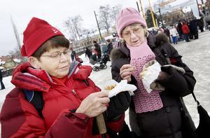 Svägerskorna Ruth Nilsson och Carin Dahlsten mumsar på varsin kolbulle. På marknaden handlar de bara saker som går att stoppa i magen.