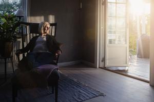 Från altanens dubbeldörrar flödar solen in i vardagsrummet till sen eftermiddag.
