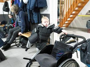 Mille sträcker sig efter benskydden på rullstolen.