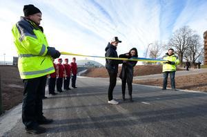 Viktor Schütt och Dina Awad klipper det symboliska invigningsbandet, som placerats vid gång- och cykelvägen mellan centrum och Kupolen.