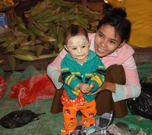 en liten burmesisk flicka med solskyddad ansikte