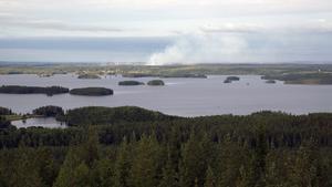 Från utsiktstornet syns röken på andra sidan Åmänningen tydligt. Längst till höger i bild syns Västervåla kyrka som en liten vit prick. Snett till vänster om den stora rökpelaren ligger Ängelsberg.