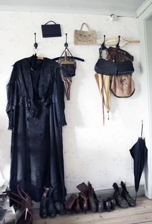 En samling snörkängor, några parasoll och vackra handväskor. Den svarta chiffongklänningen är över 100 år gammal och väntar på lagning för att kunna användas igen.