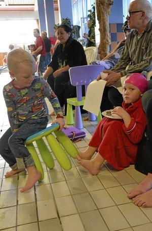 Energipåfyllning. Åttaåriga Tuva Vestberg Törling fyller på med saft och chokladboll efter simningen. Lillebror Ture, fyra år, har fortfarande mycket energi kvar trots att även han har simmat 25 meter med hjälpa av en simdyna.